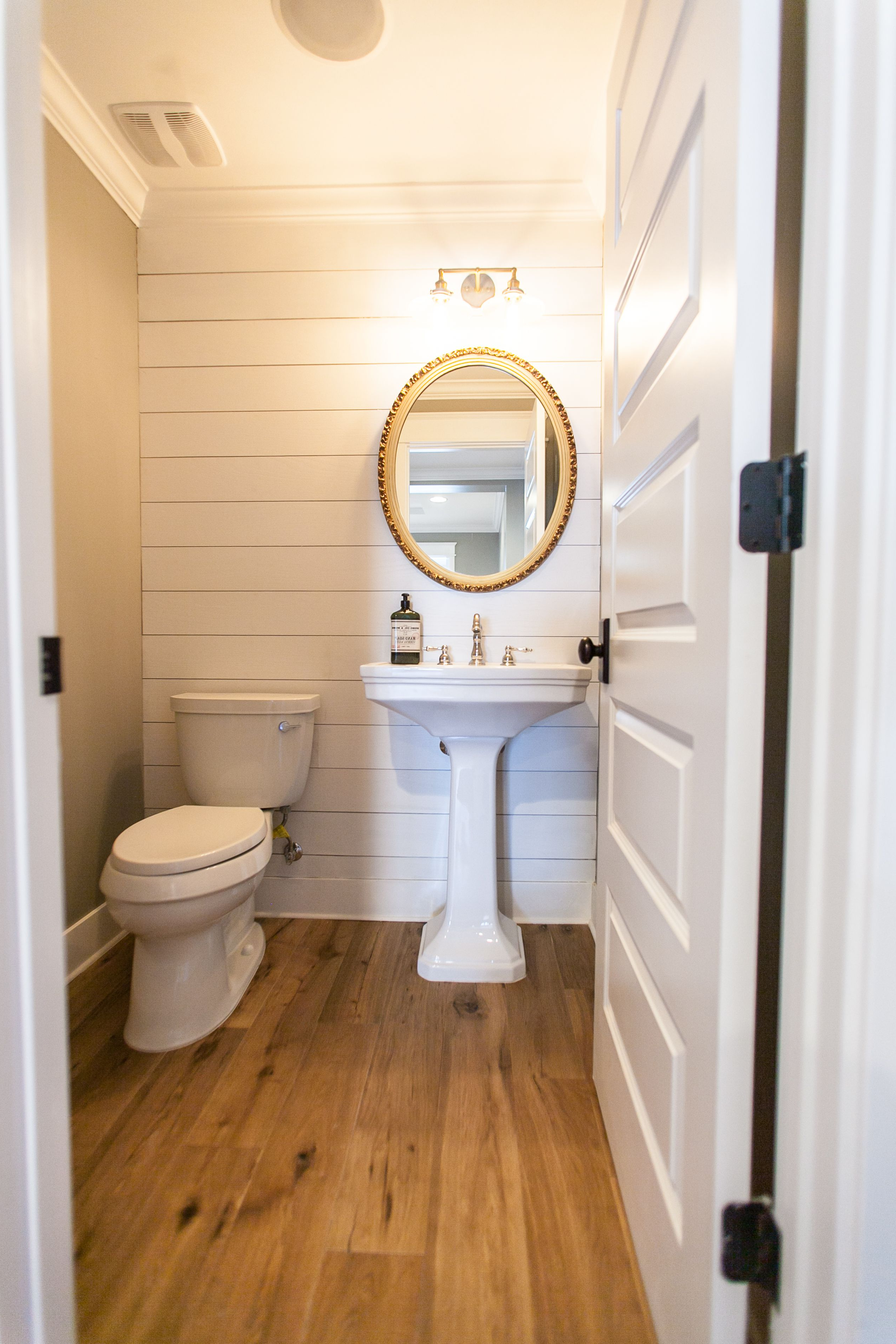 Powder Room With Planked Walls And Vintage Gold Mirror