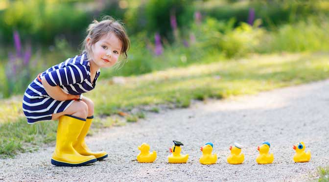 Girl looking at rubber duck representing how to pick a homeschool curriculum