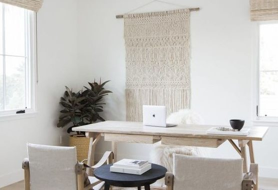 A Neutral And Simple Boho Home Office With Woven Shades And A Macrame Hanging, A Minimal Wooden Desk And Matching Chairs Plus A Black Side Table