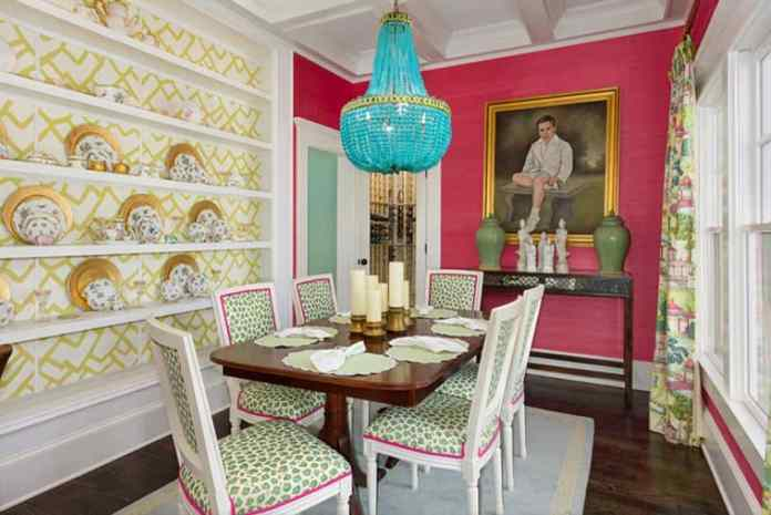 The various colors and patterns of this dining area is bonded together by the pink wall at the head of the wooden table. This table is paired with white wooden chairs with green and pink patterns. This is topped with a green chandelier hanging from a white coffered ceiling.