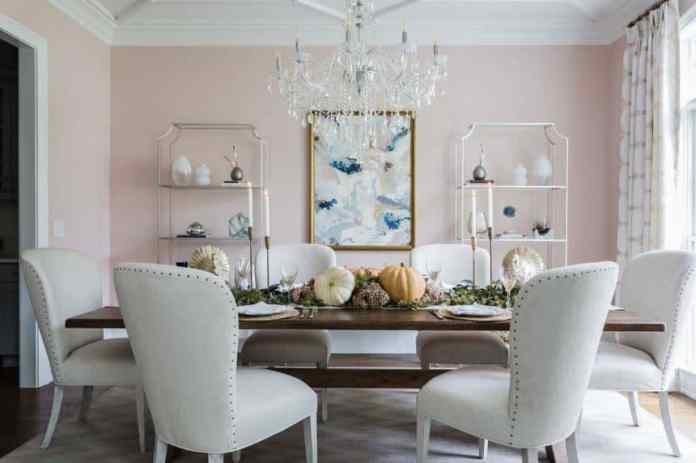 The cheerful demeanor of these light pink walls are further enhanced by the colorful abstract painting flanked with shelves that are filled with decors. This is a nice pairing with the crystal chandelier over the wooden dining table.