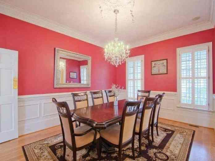 The focal point of this formal dining room is the brilliant crystal chandelier that brightens the white ceiling and white wainscoting. These bright elements are subdued by the pink upper walls that complement the dark wooden dining set.