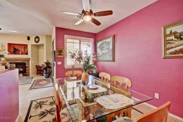 The various colorful painting that adorn the pink walls are colorful contrasts that elevate the elegance of this dining room that has a glass-top dining table surrounded by wooden chairs over an area rug with palm tree patterns on it.