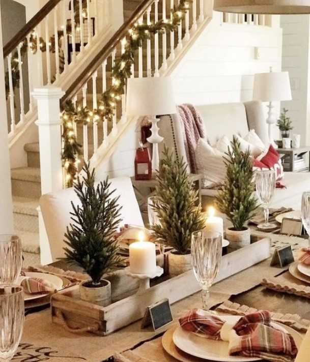 A Homey Winter Table With A Burlap Runner And Placemats, Plaid Napkins, Mini Christmas Trees, Candles, Plaid Napkins