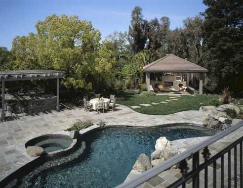 Swimming Pool With Gray Stone Patio In A Lovely Backyard