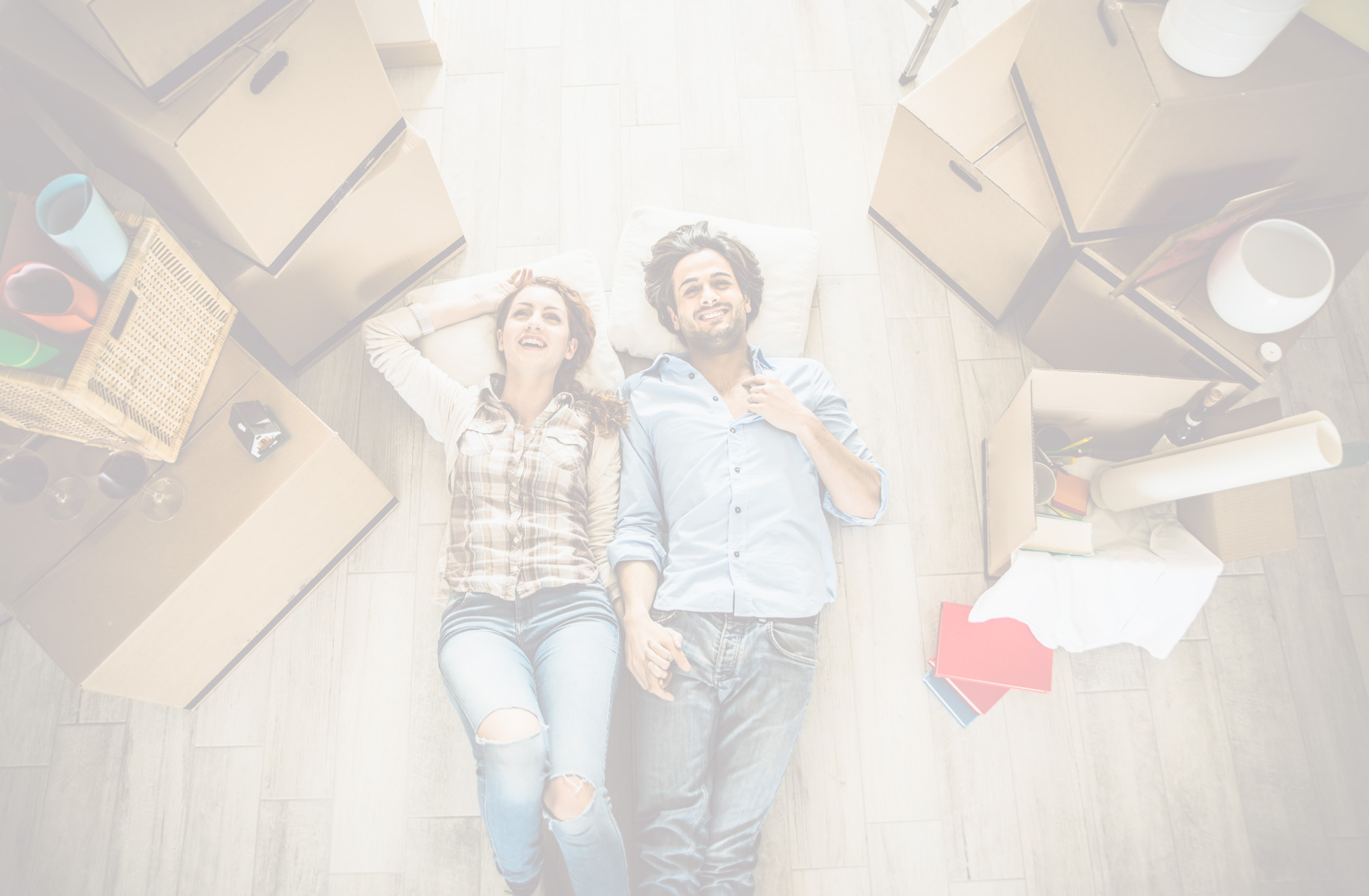 photo of couple laying on the ground surrounded by moving boxes