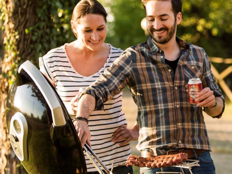 Foto van 2 mensen die grillen op een Napoleon houtskool-grill. De foto hoort bij de bbq tips.