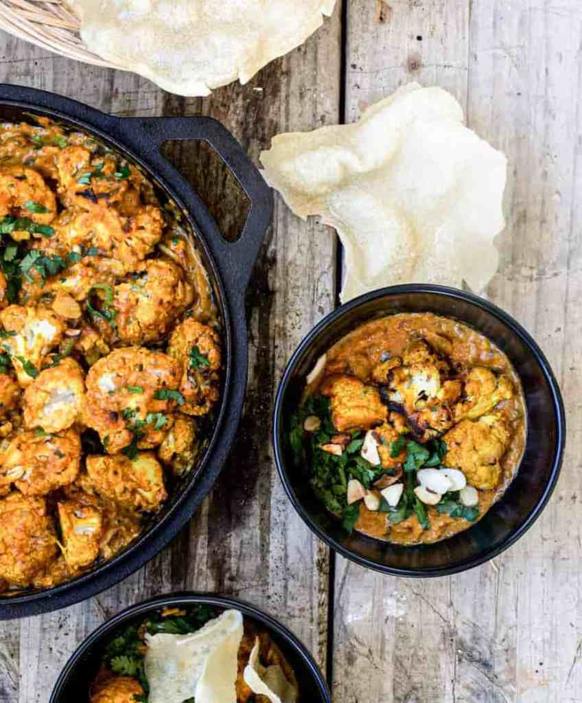 a birds eye view of black bowls of cauliflower masala topped with almonds and green corainder