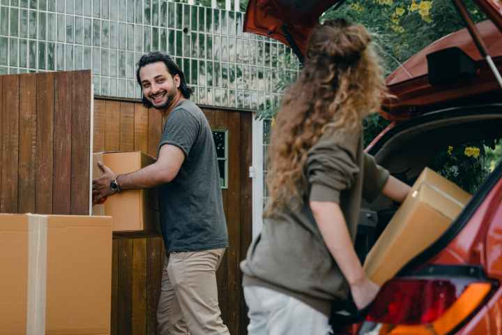 happy couple unloading automobile while moving apartment in summer day