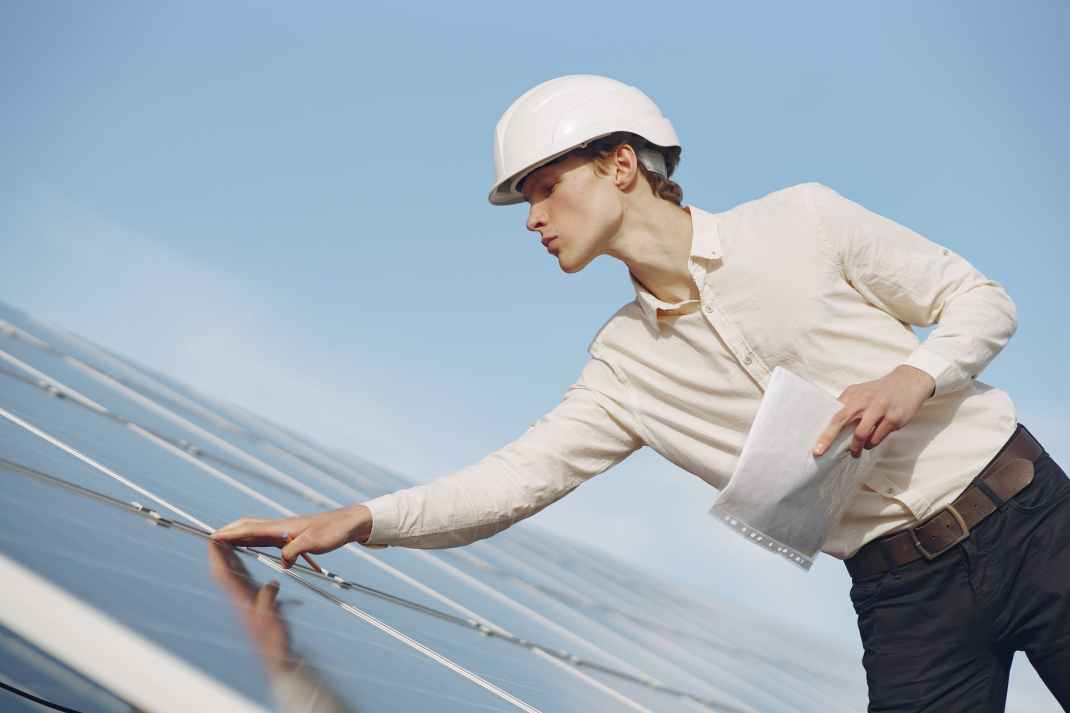 confident young man touching solar panels while working on project