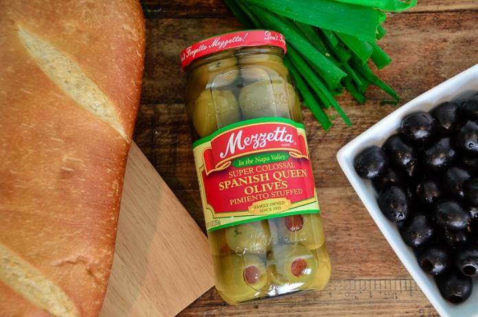 Mezzetta Spanish Queen Olives in a jar next to loaf of bread and green onions