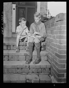 Earl Babcock watching while Howard, his brother, in his Boy Scout uniform, practices tying knots
