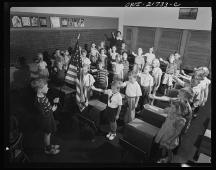 Earl Babcock's school day begins with the salute to the flag. The Bellamy Salute which is pictured here was officially replaced by the hand-over-heart salute when Congress amended the Flag Code on December 22, 1942.