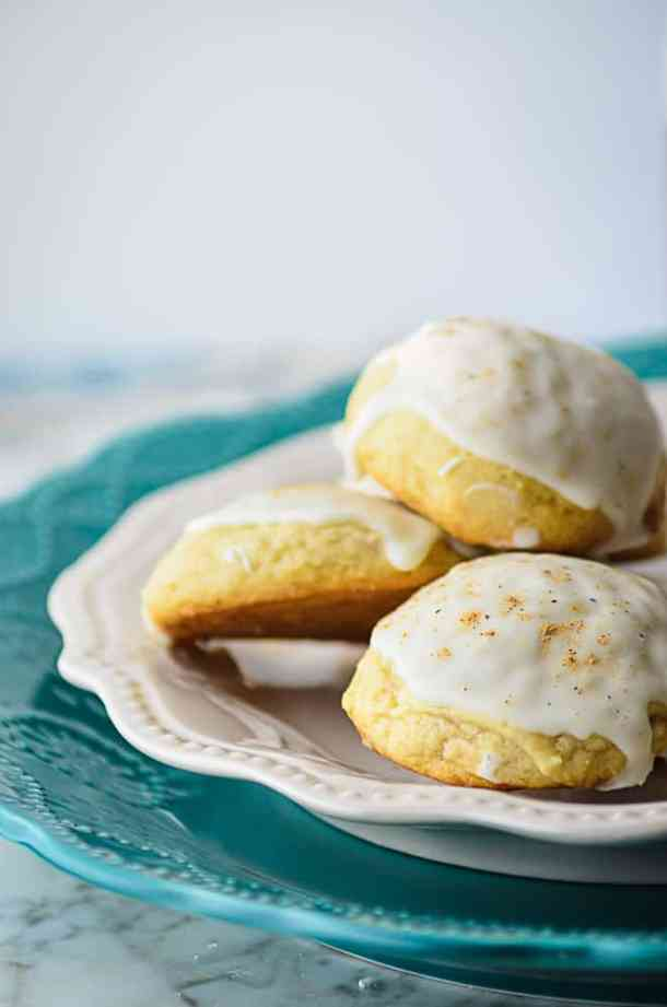 A pile of eggnog cookies staked on a white plate sitting on a teal plate on  a marble countertop.