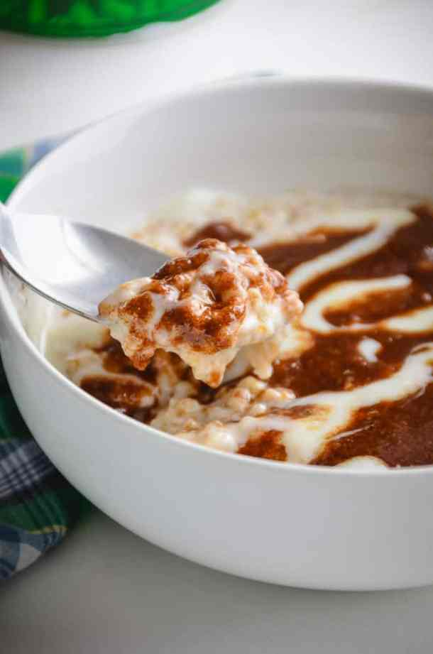 A bowl of steel cut oats topped with a brown sugar cinnamon glaze and cream cheese swirl topping,