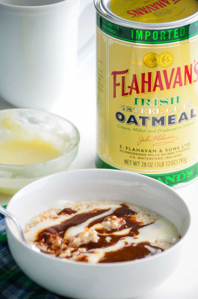 A bowl of steel cut oats topped with a brown sugar cinnamon glaze and cream cheese swirl topping, next to a canister of Flahavan's Irish Steel Cut Oats.