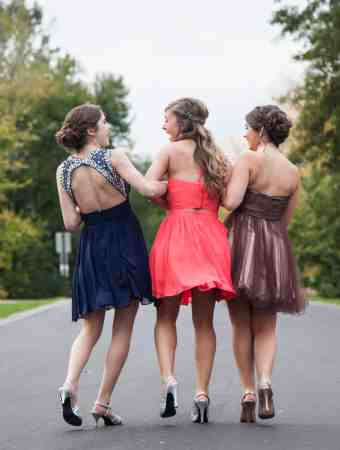 Three girls in prom dresses walking down a road chatting and laughing
