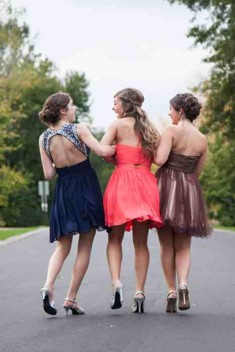 354038e1dd9e Three girls in prom dresses walking down a road chatting and laughing