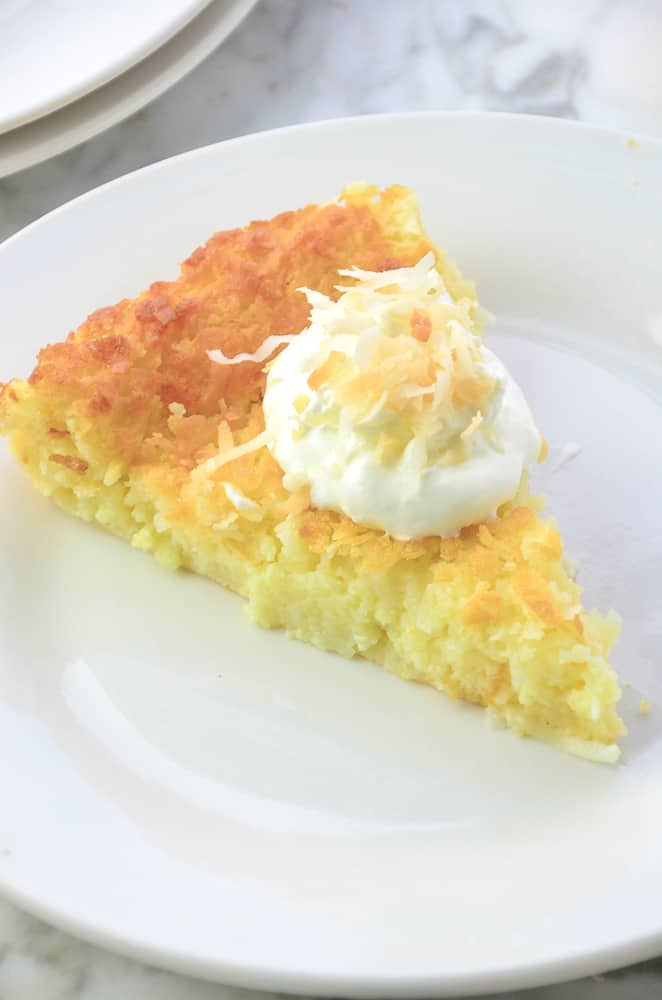 Coconut Impossible Pie on a white plate garnished with whipped cream and toasted coconut