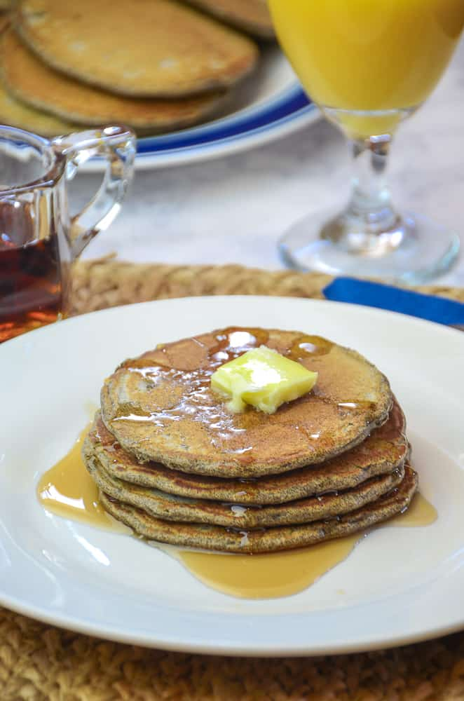 Buckwheat Pancakes drizzled with maple syrup and topped with butter on the white plate