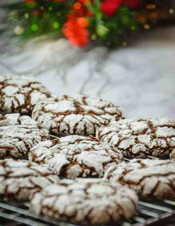 Chocolate crinkle cookies on a marble contertop with christmas greenery in the background