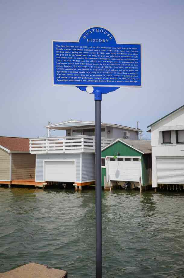 Historic Marker on Canandaigua City Pier., with boathouses in the background.