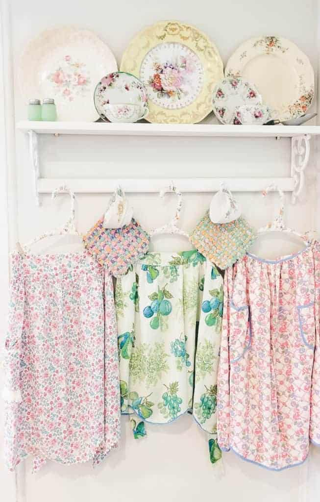 Vintage aprons with dinnerware on a white shelf in a kitchen on display.
