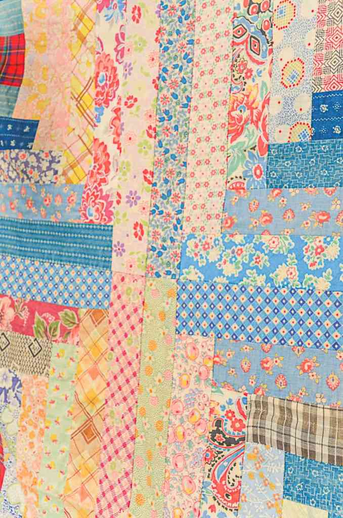 close up view of a log cabin quilt made from vintage feedsack fabric.