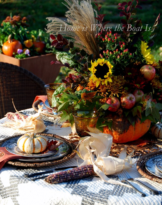 A fall table with a harvest of Indian corn, mini pumpkins and a pumpkin vase centerpiece | ©homeiswheretheboatis.ne #fall #tablescapes #pumpkinvase #alfresco