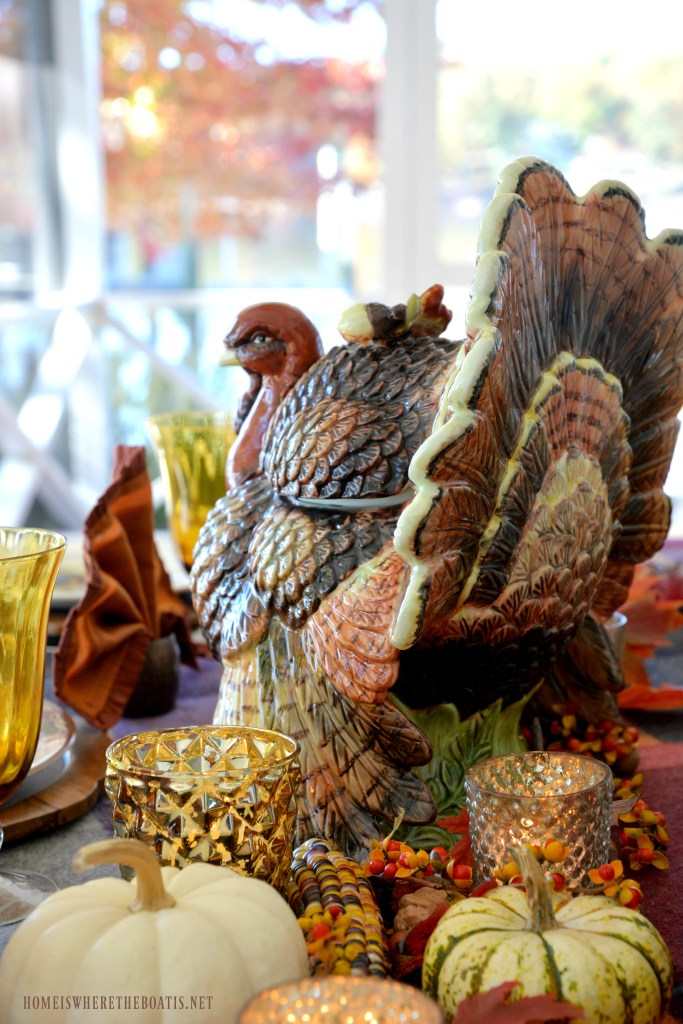 Thanksgiving table on the porch with assorted Tom Turkeys and turkey tureen centerpiece | ©homeiswheretheboatis.net #Thanksgiving #tablescape #tablesetting #turkey