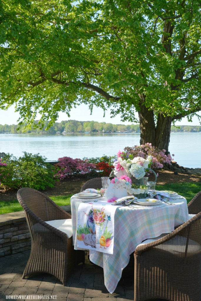Alfresco table with a blooming watering can, butterflies and bunny and chick with eggs for Easter | ©homeiswheretheboatis.net| ©homeiswheretheboatis.net