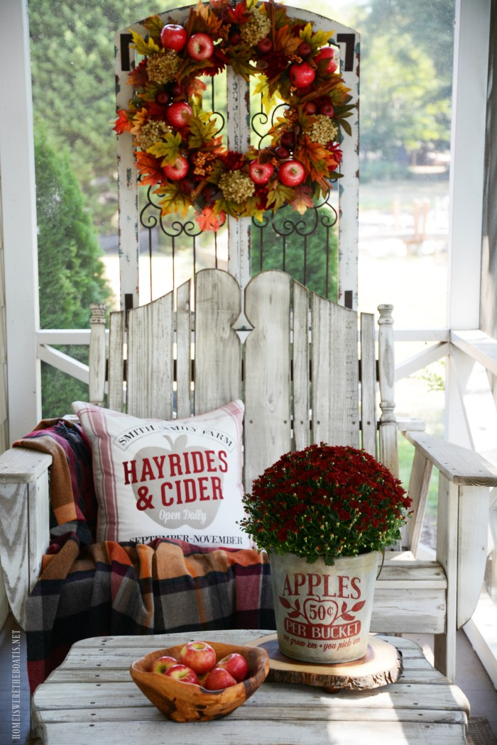 Mums in apple bucket and Apples on the Porch | ©homeiswheretheboatis.net #fall #porch #wreath #apples