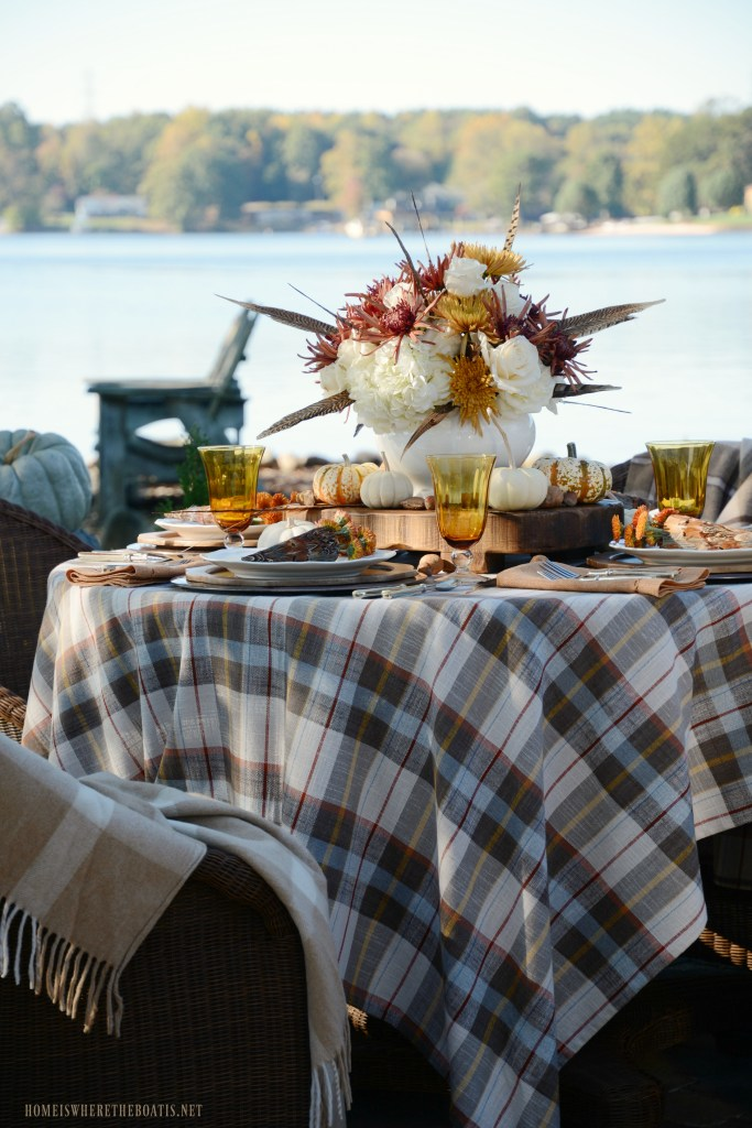 Lakeside fall table with plaid, feathers and pumpkins | ©homeiswheretheboatis.net #fall #tablescape #alfresco #flowers #feathers