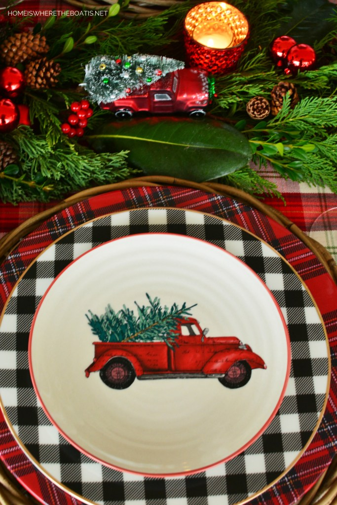 Red truck with tree salad plate with buffalo check and tartan plaid | ©homeiswheretheboatis.net #christmas #truck #tablescapes #tartan #plaid