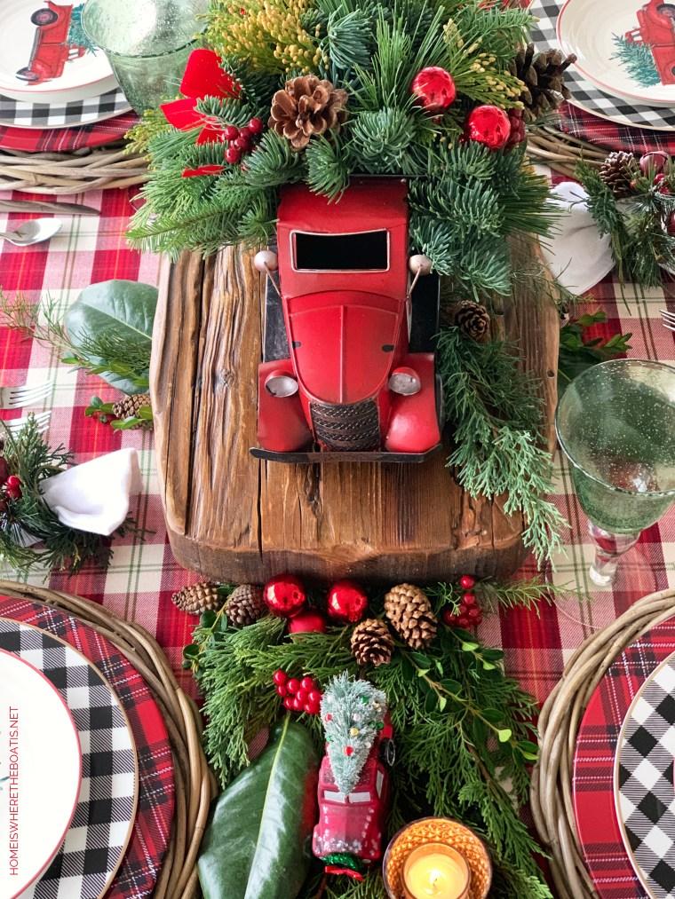 Red truck Christmas table with tree salad plates, buffalo check and tartan plaid | ©homeiswheretheboatis.net #christmas #truck #tablescapes #tartan #plaid
