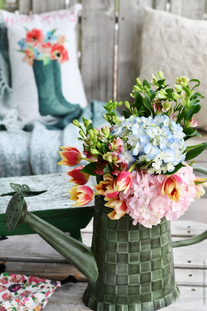 Spring on the porch with flowers in watering can | ©homeiswheretheboatis.net #flowers #spring
