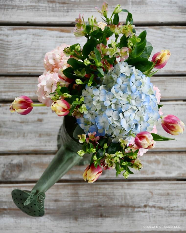 Flowers in watering can | ©homeiswheretheboatis.net #flowers #spring