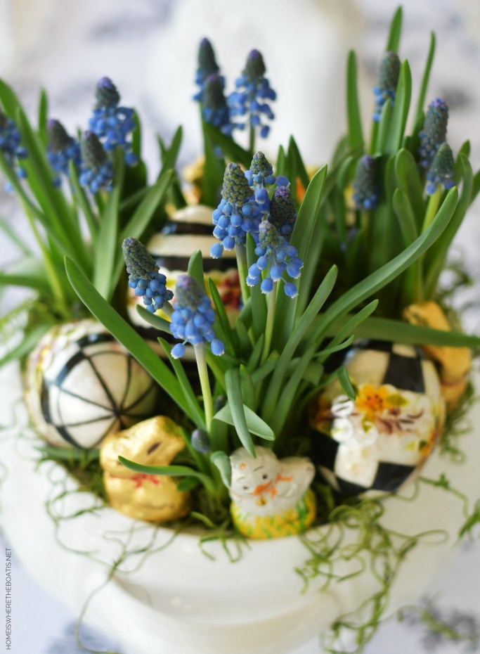Easter centerpiece with grape hyacinths, eggs, and mini Lindt chocolate bunnies and chicks | ©homeiswheretheboatis.net #easter #tablescapes