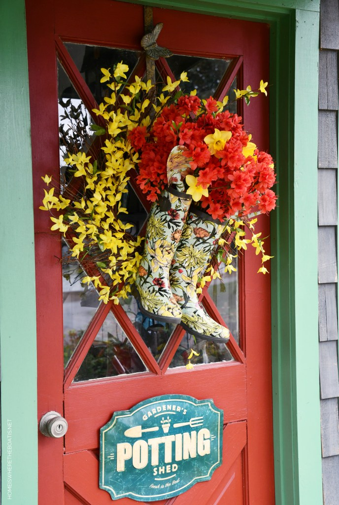 DIY Spring Wreath with blooming wellies for Potting Shed | ©homeiswheretheboatis.net #spring #wreath #diy #flowers