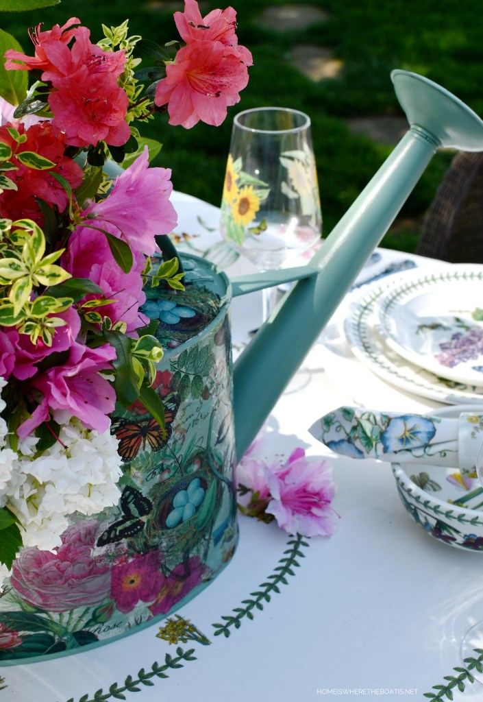 Watering can centerpiece with flowers | ©homeiswheretheboatis.net #tablescapes #alfresco #spring #flowers