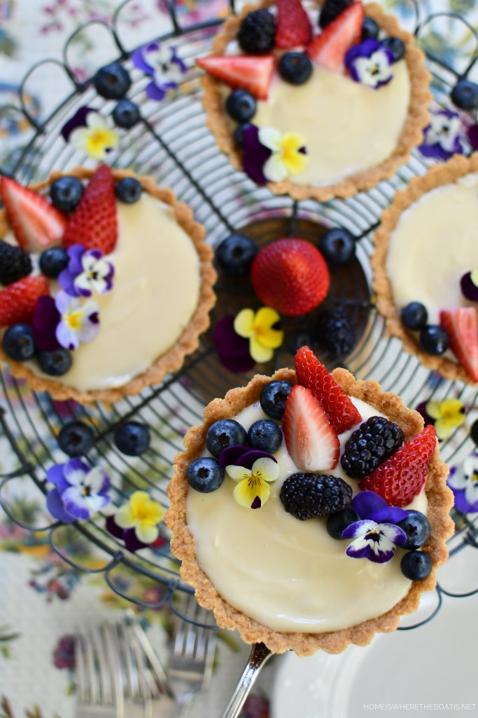 Mini Lemon Curd and Cream Cheese Tarts with Cookie Crust, Berries and Edible Flowers | ©homeiswheretheboatis.net #tarts #recipes #desserts #spring #fruit #edibleflowers