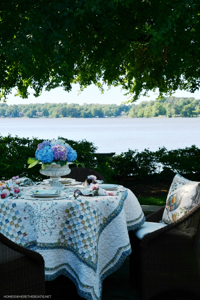 Lakeside table with hydrangeas and quilt as a tablecloth | ©homeiswheretheboatis.net #spring #alfresco #tablescapes