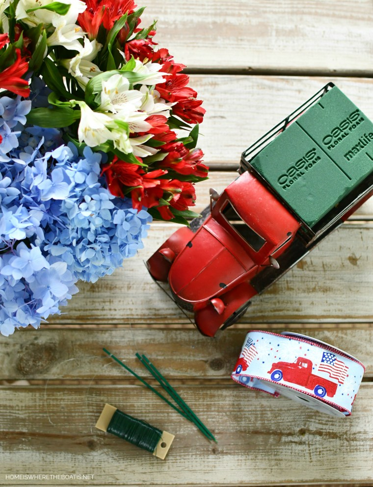 DIY patriotic flower centerpiece with a red truck | ©homeiswheretheboatis.net #patriotic #tablescape #centerpiece #flag #4thofjuly