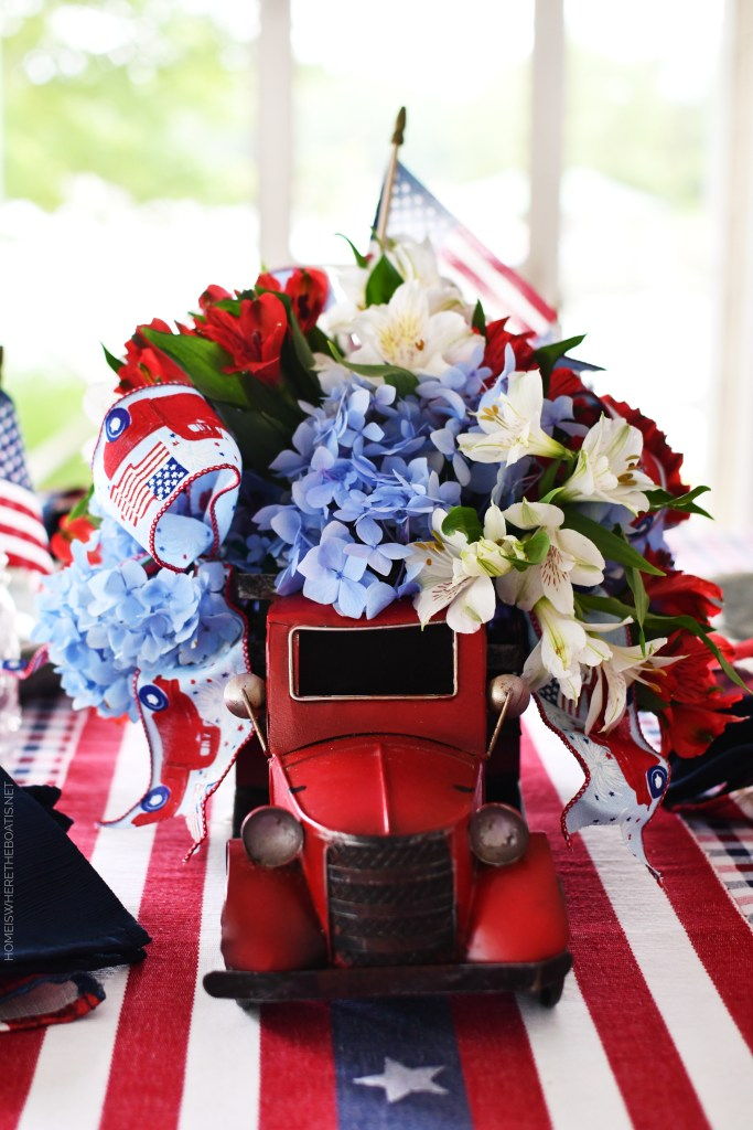 Red truck flower centerpiece and tablescape for the 4th of July | ©homeiswheretheboatis.net #patriotic #tablescapes #centerpiece #flag #4thofjuly #redwhiteandblue