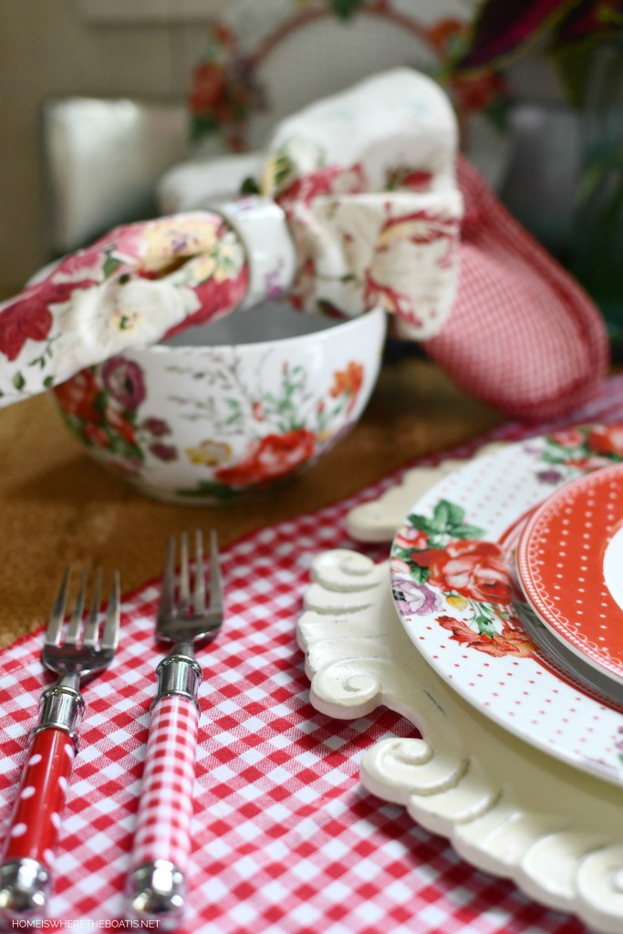Vintage-inspired floral dinnerware with gingham checks and polka dots | ©homeiswheretheboatis.net #tablescapes #redandwhite #flowers