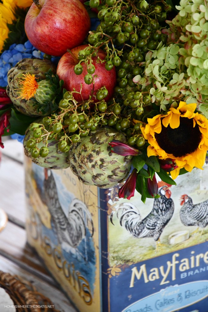DIY transitional flower arrangement in biscuit tin incorporating artichokes and apples   ©homeiswheretheboatis.net #hydrangeas #sunflowers