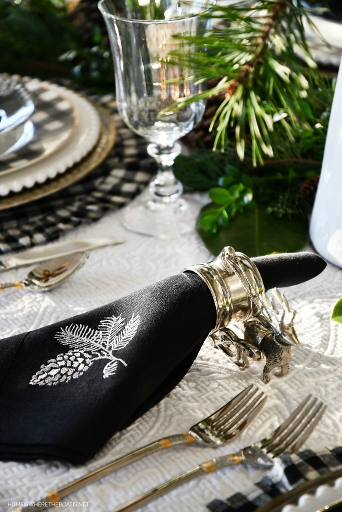 Christmas tablescape with reindeer napkin rings, pinecone linen napkins and black and white checks | ©homeiswheretheboatis.net #christmas #tablescapes