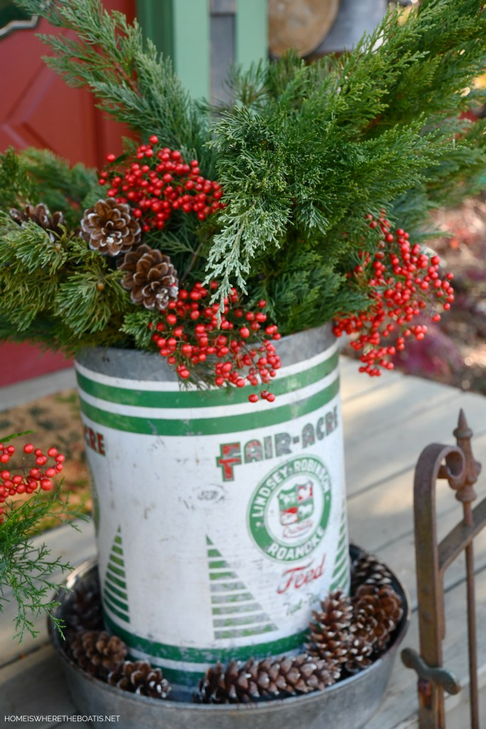 Vintage Fair-Acre Feed chicken feeder filled with greenery, pine cones and Nandina berries | ©homeiswheretheboatis.net #shed #christmas #greenery