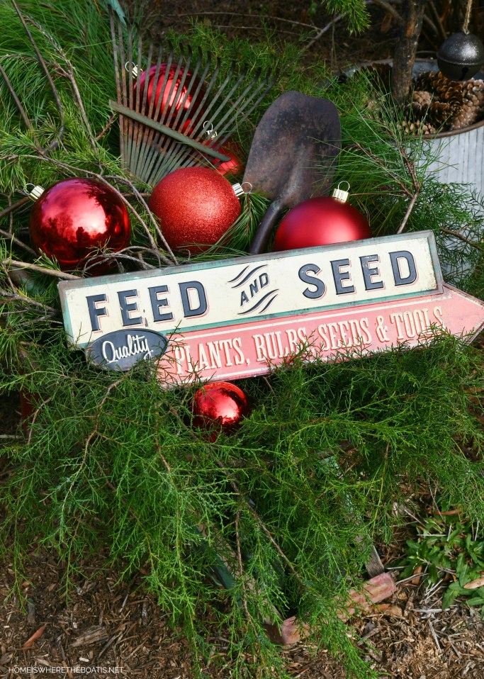 Feed and Seed Quality Plants, Bulbs, Seeds & Tools sign in wheelbarrow with garden tools and ornaments for Christmas | ©homeiswheretheboatis.net #shed #christmas #greenery #garden
