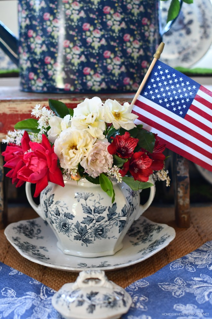 Red, White and Blue tablescape with vintage transferware, flowers and flag for Memorial Day | ©homeiswheretheboatis.net #redwhiteandblue #transferware #flowers #tablescape #memorialday #patriotic